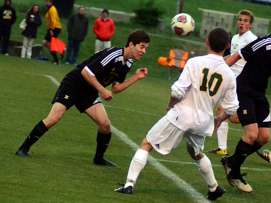 Hendersonville High senior Cole Egan heads a ball away from the box during first-half action. Egan scored on a penalty kick in the Commandos' 2-0 victory on Thursday evening.