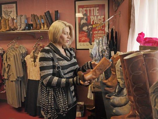 Longtime customer GiGi LaFemme looks through boots