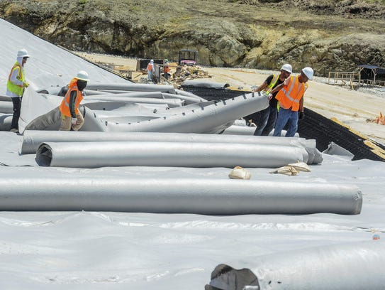 Workers prepare to install a sheet of geomembrane material