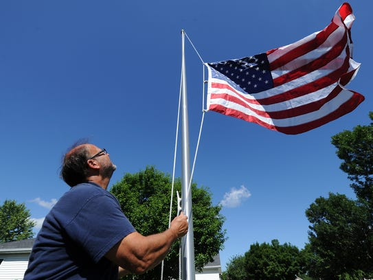 George Rapp of Fly-Me-Flag installs a 20-foot flagpole