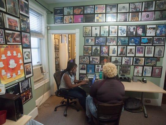 Dannyelle Austin (left) speaks with a girl at Hopeworks
