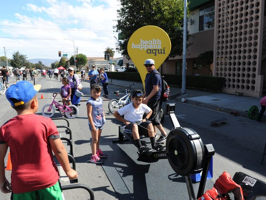 Children try out workout equipment during Ciclovia