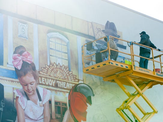 Workers paint a mural on the old Zelphy's Liberation