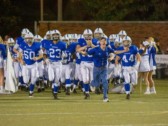 Aaron Coomer leads the Memorial Tigers on to the field