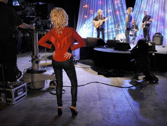 Dolly Parton listens as Chris Stapleton records his