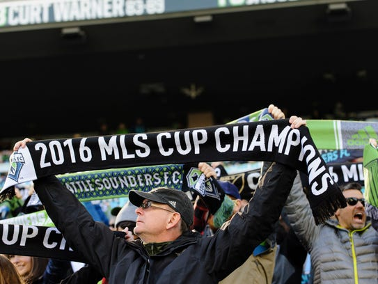 A Seattle Sounders fan holds up a championship scarf