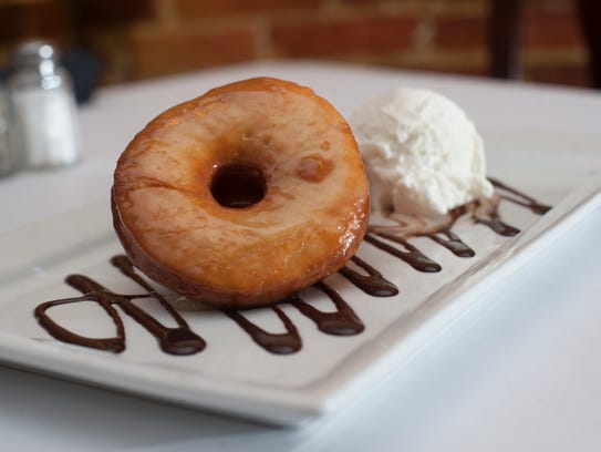 A house-made doughnut  with ice cream tops off a meal