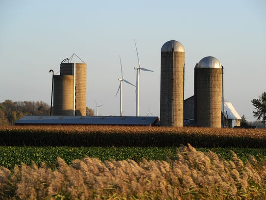 Wind turbines turn amid farm silos at DTE's Sigel wind