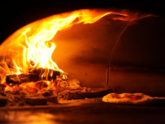 Flames crawl up the sides of the pizza oven as a pizza