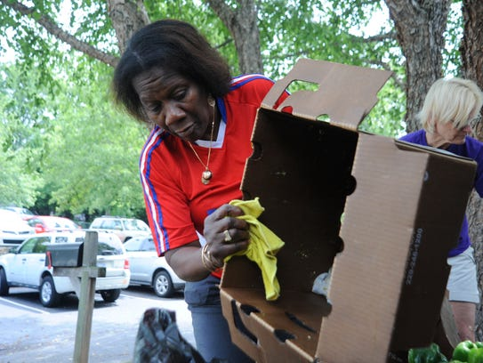 Marcela Jackson empties a box of bell peppers on June