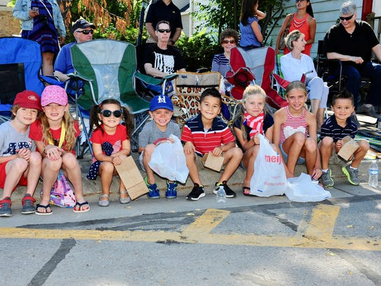 Kids line up along Main Street with smiles as they