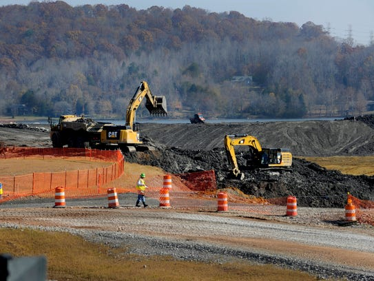 TVA contract workers remove coal ash from the edge