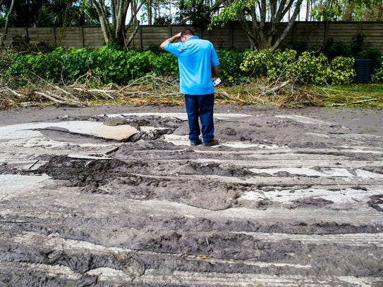 A Collier County worker observes where sewage broke