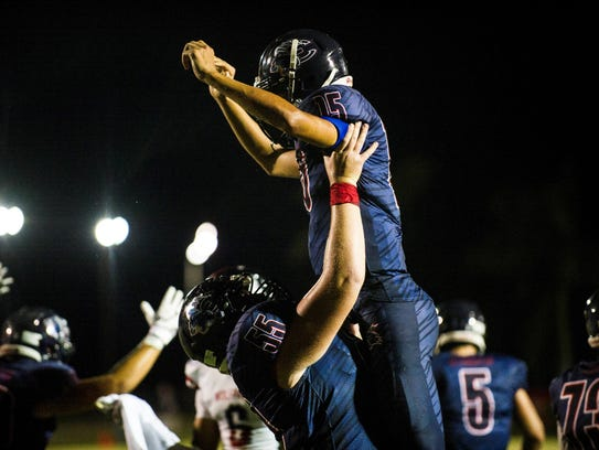 Estero High School quarterback Tanner Elliott is lifted
