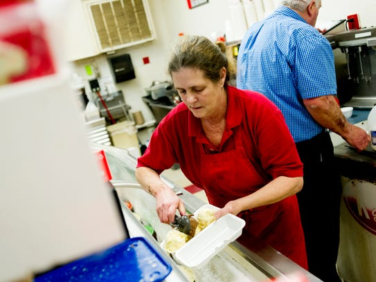 A worker prepares an ice cream at Kay's Ice Cream on