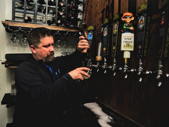 Eric Camper, head brewer at Tall Tales, pours Key'd