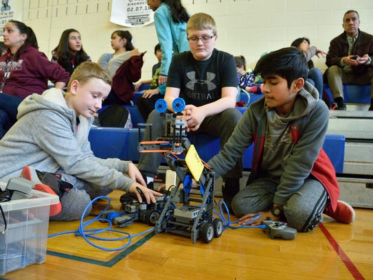 Szymon Kowal, 11, Chris Zawadski, 12 and Aidan Almeida of the Faust School in East Rutherford prepare their robot for competition in the Vex IQ Robotics Tournament at the Carlstadt Public School on Wednesday.