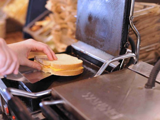 A classic grilled cheese is placed on the burner at