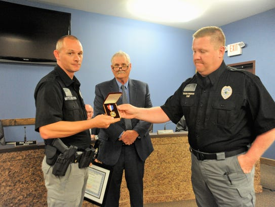 As mayor Don Collins looks on, Black Mountain police chief Shawn Freeman, right, presents a life-saving medal to sergeant Chris Staton.