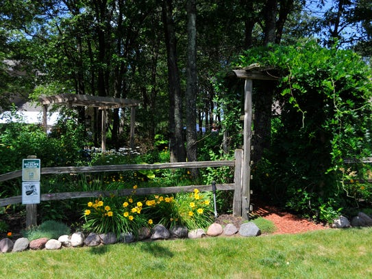 A vine-covered gate leads to a shaded garden path,