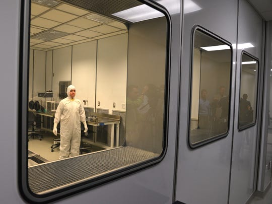 Workers in the clean room monitor radiation samples