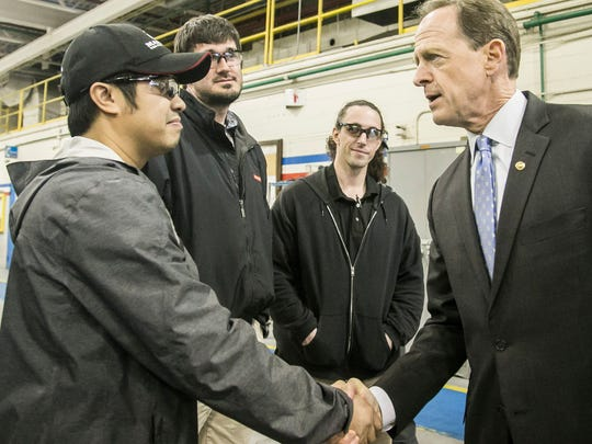 Sen. Pat Toomey shakes hands with Electrical Engineer Simon Nguyen, left,  during his tour of the BAE Systems Facility Friday, March 31, 2017, in West Manchester Township. Amanda J. Cain photo