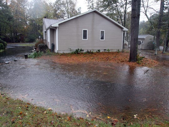 In this file photo, an Ocean Pines home's yard becomes a pond after torrential rains.
