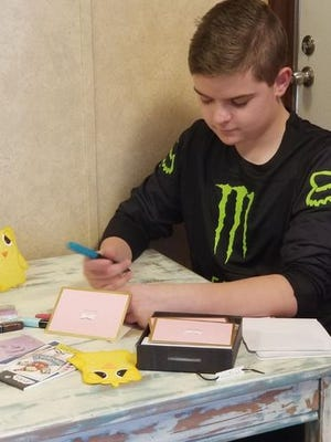 McLoud Public School student and 14-year-old Ricky Graham writing a card to his Golden Rule Home pen pal and resident Lena Winthrow.