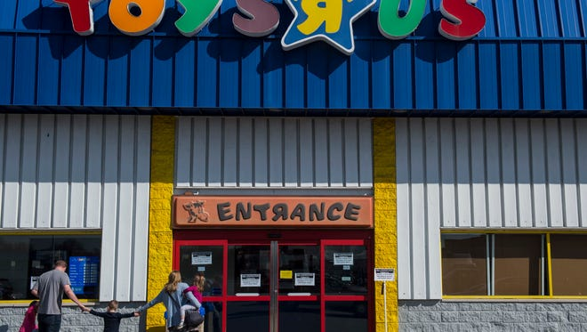 """A family walks into Toys """"R"""" Us on North Green River Road in Evansville on Thursday, March 22, 2018. A liquidation sale scheduled for Thursday was postponed until further notice."""