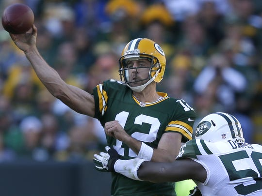 Green Bay Packers' Aaron Rodgers makes a throw before being tackled by Demario Davis of the New York Jets.