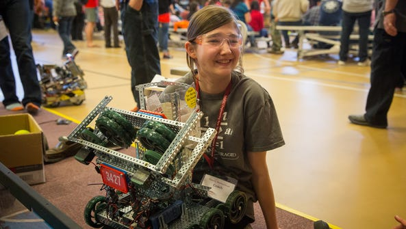 14-year-old Catriona Omdahl sits with a robot moments