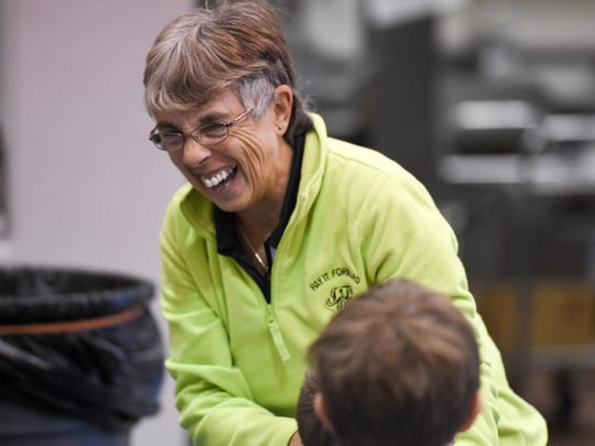 Volunteer Mary Sauter, who donated $5,000.00 to buy presents for every student, laughs as she talks with kids on Wednesday, Dec. 21, during Mitchellville Elementary's Christmas celebration.