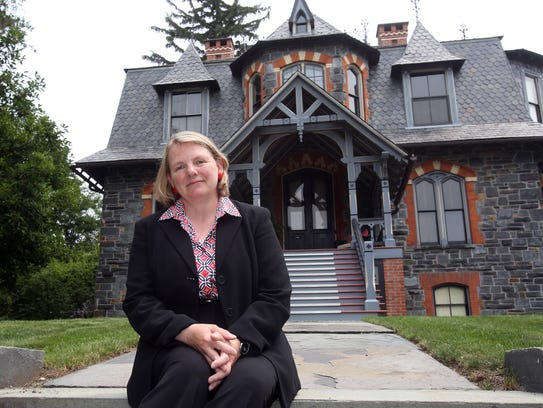 Holly Wahlberg sits in front of her historic home on