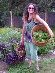 Sheryl Rapée-Adams harvests some fresh produce from The Garden at 485 Elm in Montpelier. Members of 25 households share gardening space there.