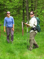Koffarnus (left) and Heisz trek through a grassy area