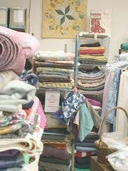 The store is filled with fabrics, yarn and other items.