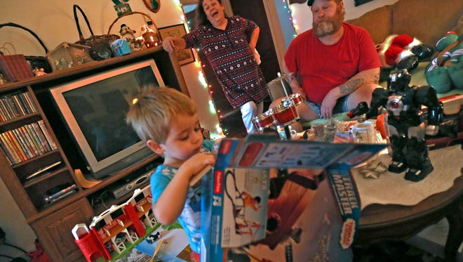Peg Oliver and her ex-husband, Ollie Oliver, watch their three-year-old grandson, Joseph Oliver Howell, open presents Christmas morning. The couple is helping to raise Joseph while his father, Kyle, is in the hospital with leukemia.