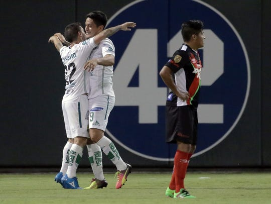 German Cano, center, celebrates his goal with teammate