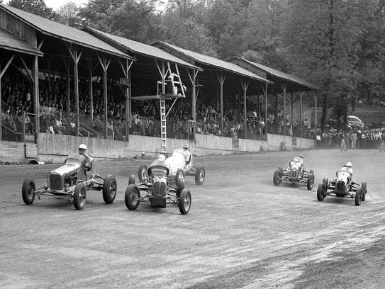 In 1942 cars speed past the spectator stands which