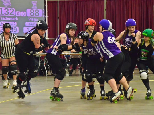 Makenna Visga, with star on helmet, scores points as a jammer during a roller derby match.
