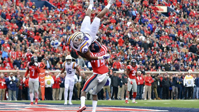 LSU Tigers wide receiver Travin Dural (83) is hit by Mississippi Rebels defensive back Kendarius Webster (15) after an incomplete pass during the first quarter of the game at Vaught-Hemingway Stadium. Dural was injured on this play and left the game.