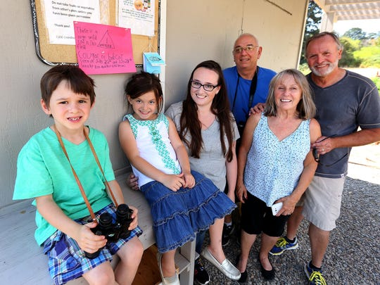 From left, twins Nolan and Mila Venti, Kari Venti, Ron Jaymot, Mary Anne Bryan and Roy Bryan stand near the warning sign Nolan and Mila created in July when they saw what the adults thought was a bobcat on a field near the Ellen Lane Community Garden. Nolan insisted then it was a cougar, and his belief was reinforced when the cat was spotted again Monday, with the classic long tail of a mountain lion.