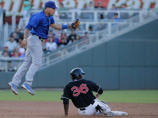 Iowa Cubs shortstop Javy Baez watches as the ball thrown to him sails over his head as El Paso Chihuahuas right fielder Rymer Liriano slides safely into second.