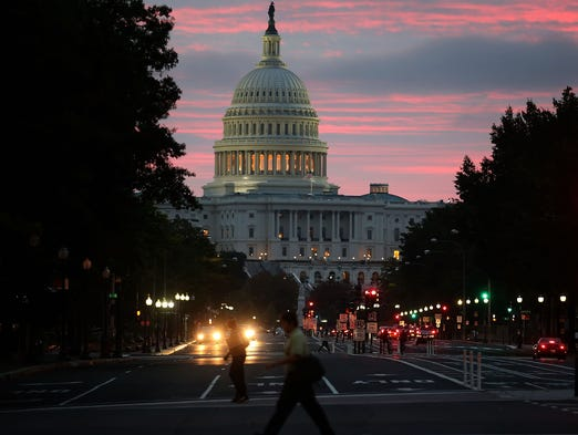 The sun begins to rise behind the Capitol building on Oct. 17 in Washington. A bipartisan bill was passed by the House and Senate to end the partial government shutdown and raise the nation's debt limit.