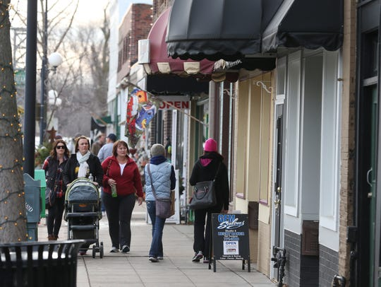 Shoppers walk by the shops in Valley Junction as part