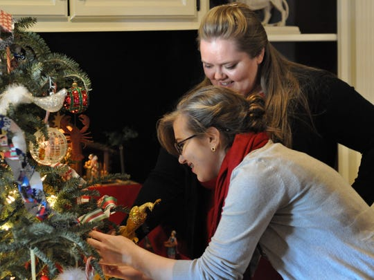 Leigh (back) and Bridget (front) Schneider arrange a new ornament just added to their Christmas tree, which will remain up through Epiphany on Wednesday. For the Alexandria family, Dec. 25 marks only the beginning of the Christmas season.