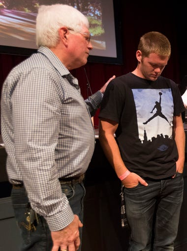 Church elder Michael McGregor (left) prays for Tyler Boyce, along with Seth Rogers and Pastor Mike Miller (right), during Corvallis Church's worship service at the Majestic Theatre in Corvallis, Ore. It was Boyce's first time in church outside prison. Boyce was recently released from prison and will be taking part in the Home for Good program with help from that church.