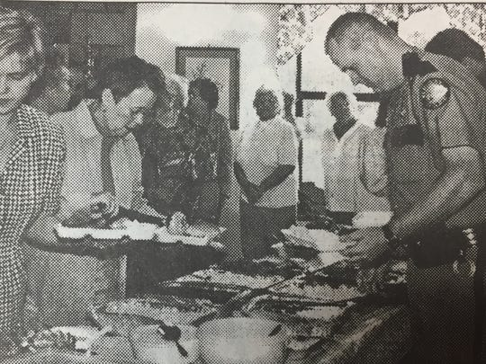 The Sturgis Senior Citizens hosted a dinner in June 2001 for county and city officials, as well as for area law enforcement agencies. Here, County Attorney Brucie Moore and Sandy Arnold, left, choose from the buffet. At right is State Trooper Bryan Whitaker.
