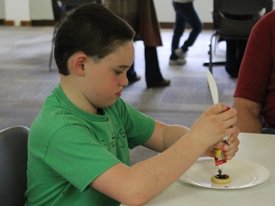Hunter Buchanan, 9, carefully concentrates as he decorates a cookie.
