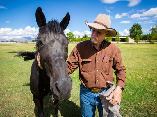 Robert Barnard, a founder of the Rockin' Horse Riding Academy, shares a moment with quarterhorse Karma. Karma was donated to be given to a veteran with PTSD, Barnard said.